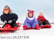 Купить «happy little kids sliding down on sleds in winter», фото № 29277570, снято 10 февраля 2018 г. (c) Syda Productions / Фотобанк Лори