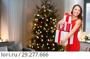 Купить «smiling woman with christmas gifts at home», фото № 29277666, снято 22 сентября 2013 г. (c) Syda Productions / Фотобанк Лори