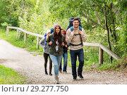 Купить «happy friends or travelers hiking with backpacks», фото № 29277750, снято 31 августа 2014 г. (c) Syda Productions / Фотобанк Лори
