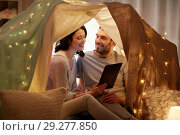Купить «happy couple with tablet pc in kids tent at home», фото № 29277850, снято 27 января 2018 г. (c) Syda Productions / Фотобанк Лори