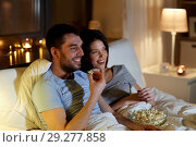 Купить «couple with popcorn watching tv at night at home», фото № 29277858, снято 27 января 2018 г. (c) Syda Productions / Фотобанк Лори