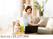 Купить «working mother with baby calling on smartphone», фото № 29277994, снято 12 мая 2018 г. (c) Syda Productions / Фотобанк Лори