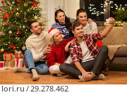 friends celebrating christmas and taking selfie. Стоковое фото, фотограф Syda Productions / Фотобанк Лори