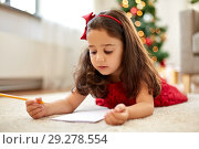 little girl writing christmas wish list at home. Стоковое фото, фотограф Syda Productions / Фотобанк Лори