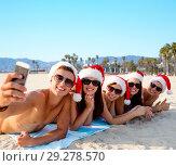 Купить «happy friends taking selfie on beach on christmas», фото № 29278570, снято 3 августа 2014 г. (c) Syda Productions / Фотобанк Лори