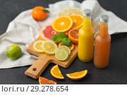 Купить «glass bottles of fruit juice on slate table top», фото № 29278654, снято 4 апреля 2018 г. (c) Syda Productions / Фотобанк Лори