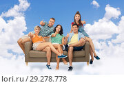 friends sitting on sofa and showing thumbs in sky. Стоковое фото, фотограф Syda Productions / Фотобанк Лори