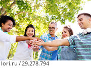 Купить «happy smiling friends stacking hands in park», фото № 29278794, снято 10 июня 2018 г. (c) Syda Productions / Фотобанк Лори