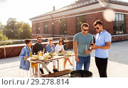 Купить «happy friends having bbq party on rooftop», фото № 29278814, снято 2 сентября 2018 г. (c) Syda Productions / Фотобанк Лори