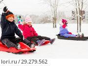 Купить «happy little kids sliding on sleds in winter», фото № 29279562, снято 10 февраля 2018 г. (c) Syda Productions / Фотобанк Лори