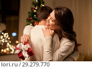 Купить «happy couple with christmas gift hugging at home», фото № 29279770, снято 11 января 2018 г. (c) Syda Productions / Фотобанк Лори