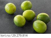 Купить «close up of whole limes on slate table top», фото № 29279814, снято 4 апреля 2018 г. (c) Syda Productions / Фотобанк Лори