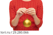 Купить «close up of woman in sweater with christmas ball», фото № 29280066, снято 10 сентября 2014 г. (c) Syda Productions / Фотобанк Лори