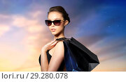 Купить «happy woman in black sunglasses with shopping bags», фото № 29280078, снято 9 апреля 2016 г. (c) Syda Productions / Фотобанк Лори