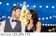 Купить «couple with party props over christmas tree lights», фото № 29280110, снято 15 декабря 2017 г. (c) Syda Productions / Фотобанк Лори