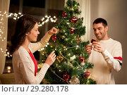 Купить «happy couple decorating christmas tree at home», фото № 29280178, снято 11 января 2018 г. (c) Syda Productions / Фотобанк Лори