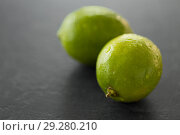 Купить «close up of whole limes on slate table top», фото № 29280210, снято 4 апреля 2018 г. (c) Syda Productions / Фотобанк Лори