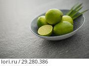 Купить «close up of limes in bowl on slate table top», фото № 29280386, снято 4 апреля 2018 г. (c) Syda Productions / Фотобанк Лори