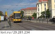 Купить «Современный желтый трамвай на остановке общественного транспорта солнечным днем. Дрезден, Германия», видеоролик № 29281234, снято 29 апреля 2018 г. (c) Виктор Карасев / Фотобанк Лори