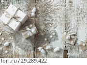 Купить «Christmas gifts on old wooden background», фото № 29289422, снято 13 октября 2018 г. (c) Майя Крученкова / Фотобанк Лори