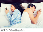 Купить «Couple with smartphones separately in bed», фото № 29289526, снято 31 мая 2020 г. (c) Яков Филимонов / Фотобанк Лори