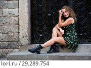Купить «Young girl tourist in dress sitting at stone stair near wall in center of Barcelona», фото № 29289754, снято 24 сентября 2018 г. (c) Яков Филимонов / Фотобанк Лори