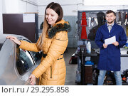 Smiling female is satisfied of tire winter replacement of her car. Стоковое фото, фотограф Яков Филимонов / Фотобанк Лори