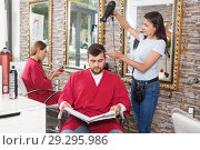 Купить «Young woman hairstylist drying hair with fen of man client», фото № 29295986, снято 25 апреля 2018 г. (c) Яков Филимонов / Фотобанк Лори