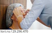 Купить «Woman in a cosmetology clinic. Specialist sticks in a needle in clients forehead», видеоролик № 29296470, снято 16 июля 2019 г. (c) Константин Шишкин / Фотобанк Лори