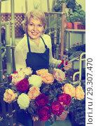 Купить «Female florist happily holding big bouquet with peonies», фото № 29307470, снято 14 ноября 2018 г. (c) Яков Филимонов / Фотобанк Лори