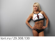 Купить «athletic beautiful blonde girl wears sportswear against a gray wall», фото № 29308130, снято 10 октября 2018 г. (c) Restyler Viacheslav / Фотобанк Лори