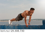 Купить «Young man training core muscles at the beach», фото № 29308730, снято 9 сентября 2018 г. (c) Pavel Biryukov / Фотобанк Лори