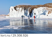 Купить «Tourists travel on the ice of the frozen Lake Baikal and take pictures of the beautiful icy rocks of Olkhon Island on a sunny winter day», фото № 29308926, снято 11 февраля 2018 г. (c) Виктория Катьянова / Фотобанк Лори