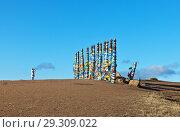 Купить «Lake Baikal. Olkhon Island. Village Khuzhir. Tourist photographs the Pillars with prayer flags and colored ribbons at the entrance to Cape Burkhan», фото № 29309022, снято 14 октября 2018 г. (c) Виктория Катьянова / Фотобанк Лори