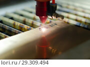 Stage of manufacturing, laser engraving in automatic mode, close-up, blurred background. Стоковое фото, фотограф Евгений Харитонов / Фотобанк Лори