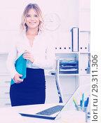 Купить «Well-wishing girl with folder of documents is standing in well-lit office», фото № 29311306, снято 17 октября 2017 г. (c) Яков Филимонов / Фотобанк Лори
