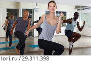 Купить «Group of happy young females and men enjoying dance techniques together», фото № 29311398, снято 30 июля 2018 г. (c) Яков Филимонов / Фотобанк Лори