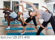 Group of active young people exercising hatha yoga pose at gym. Стоковое фото, фотограф Яков Филимонов / Фотобанк Лори