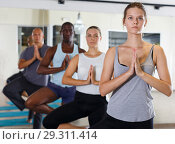 Купить «Sporty adult girls and men training yoga asana at modern studio», фото № 29311414, снято 30 июля 2018 г. (c) Яков Филимонов / Фотобанк Лори