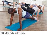Купить «People doing stretching exercises in pairs», фото № 29311430, снято 30 июля 2018 г. (c) Яков Филимонов / Фотобанк Лори