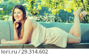 Купить «Female is posing playfully on bench in her free time», фото № 29314602, снято 10 июня 2017 г. (c) Яков Филимонов / Фотобанк Лори
