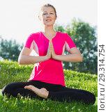 Купить «Smiling adult woman in pink T-shirt is sitting and doing meditation», фото № 29314754, снято 10 июня 2017 г. (c) Яков Филимонов / Фотобанк Лори