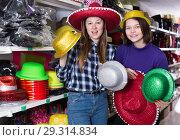 Купить «Female friends choosing funny headdresses in store», фото № 29314834, снято 15 марта 2018 г. (c) Яков Филимонов / Фотобанк Лори