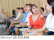 Female student talking with groupmates during classes. Стоковое фото, фотограф Яков Филимонов / Фотобанк Лори