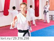 Купить «Preteen boy practicing karate movements with male trainer supervision», фото № 29316298, снято 3 июля 2020 г. (c) Яков Филимонов / Фотобанк Лори