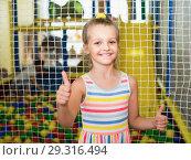 Купить «Smiling small girl showing thumbs up on indoor», фото № 29316494, снято 18 июня 2019 г. (c) Яков Филимонов / Фотобанк Лори