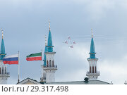 """Kazan, Russian Federation - Oktober 27, 2018: Aerobatics performed by aviation group of Military-air forces of Russia """"Strizhi"""". Kul Sharif mosque and flags of Russia and Tatarstan on the foreground. Редакционное фото, фотограф Константин Шишкин / Фотобанк Лори"""