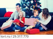 Купить «Beautiful family members presenting gifts on Christmas», фото № 29317770, снято 23 января 2019 г. (c) Яков Филимонов / Фотобанк Лори
