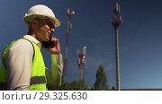 Купить «Engineer In Helmet Talking On Phone With Director», видеоролик № 29325630, снято 12 июля 2018 г. (c) Pavel Biryukov / Фотобанк Лори
