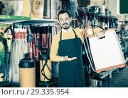 Купить «Seller displaying various items in garden equipment shop», фото № 29335954, снято 2 марта 2017 г. (c) Яков Филимонов / Фотобанк Лори